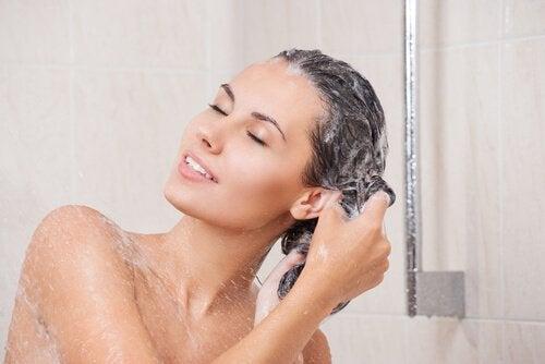 Mulher lavando cabelo longo e saudável