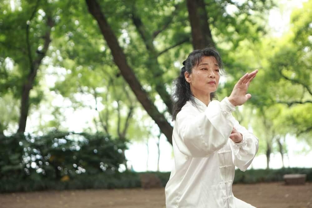 Mulher praticando tai chi no parque