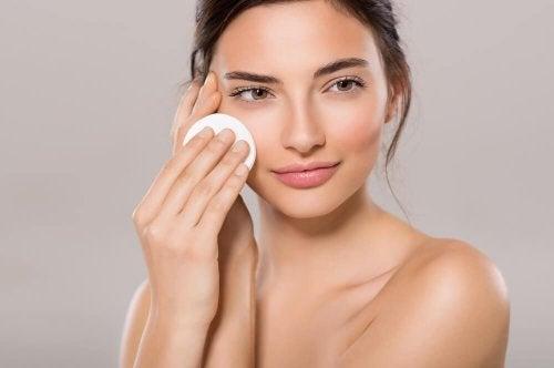 Mulher limpando a pele do rosto