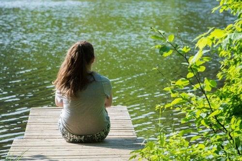 Mulher sentada sozinha olhando para a lagoa