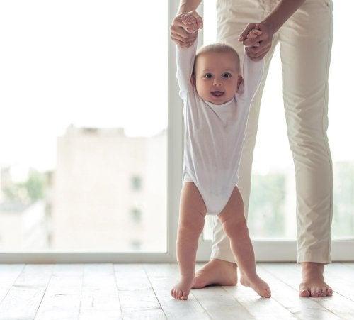 Pessoa ajudando bebê a andar