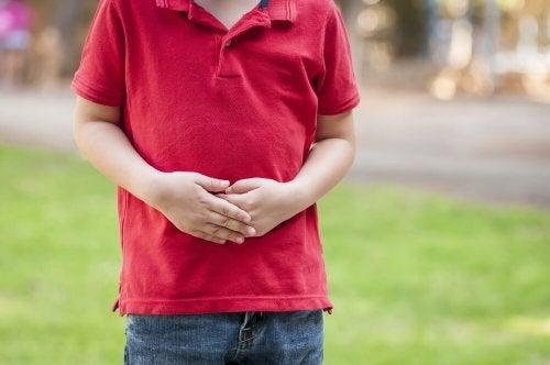 Criança com as mãos sobre a barriga
