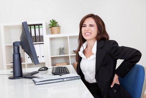 Mulher com dor nas costas no trabalho