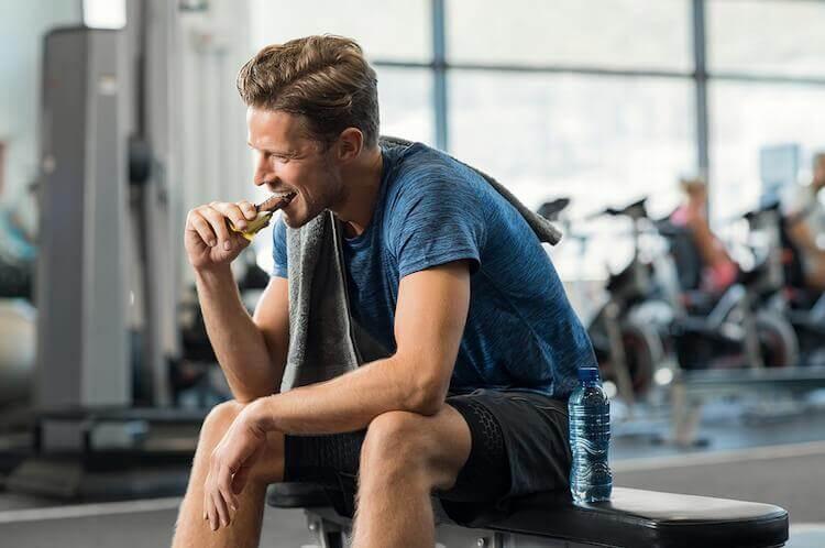 Homem comendo na academia