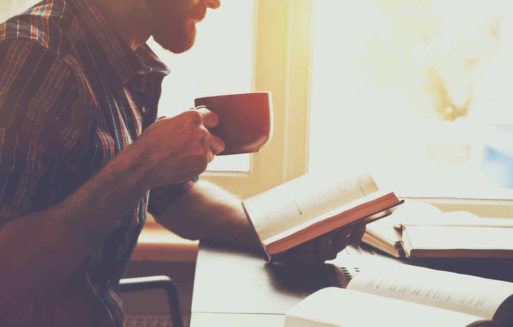 Homem lendo livro com xícara de café