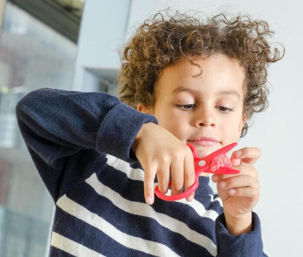 Criança usando tesoura infantil