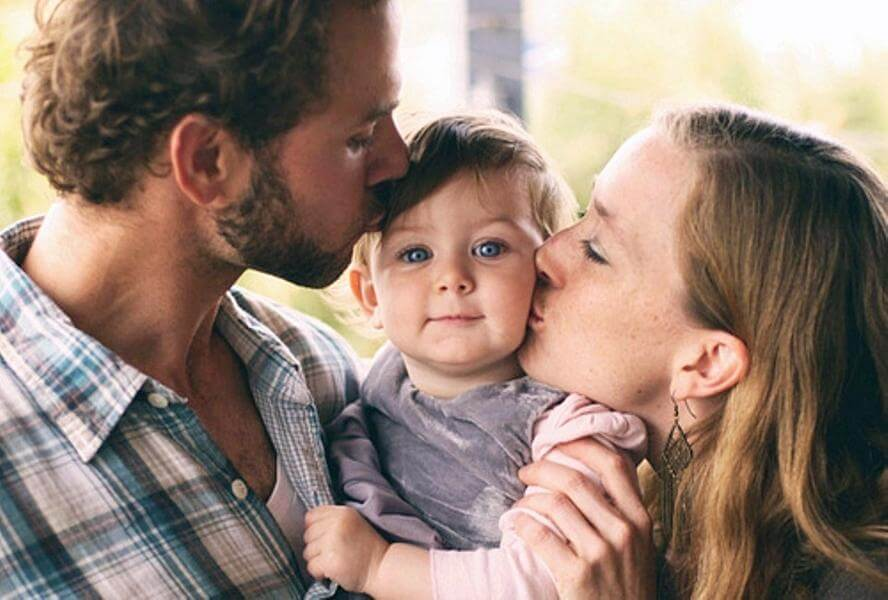 Pais beijando sua filha pequena