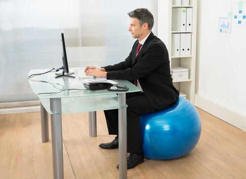 Homem trabalhando sentado em bola