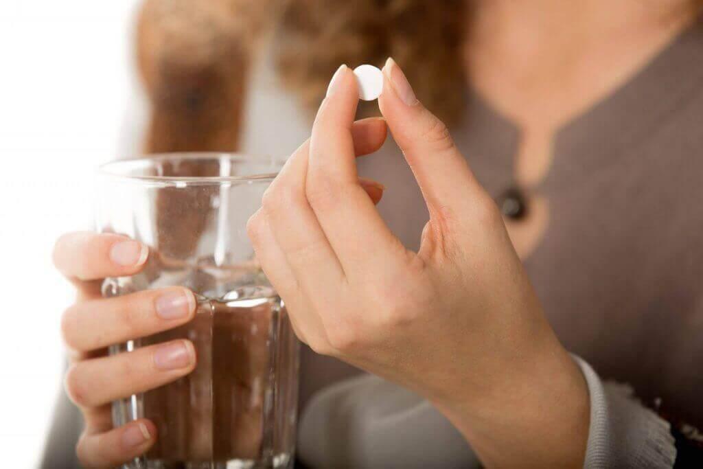 Mulher tomando remédio