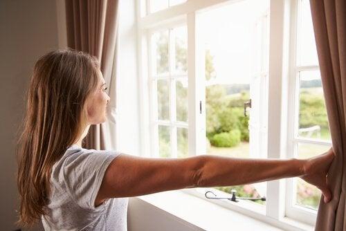 Mulher abrindo as cortinas