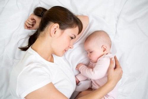 Mãe olhando o bebê dormir