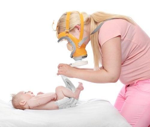 Mãe trocando fralda de bebê com diarreia infantil