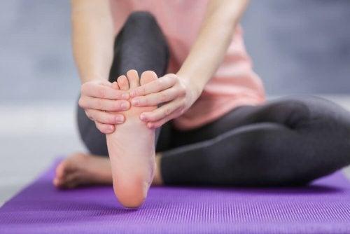 Mulher com dor nos pés provocado pelo uso de chinelos de praia