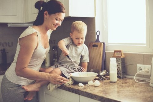 Mãe ensinando filho com problemas de aprendizagem a cozinhar