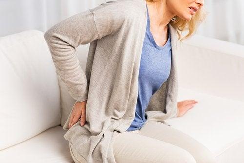 Mulher com dor lombar que pode indicar a presença de pedras nos rins