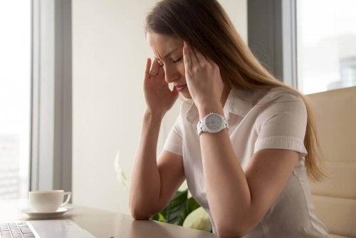 Mulher com dor de cabeça por causa do cansaço