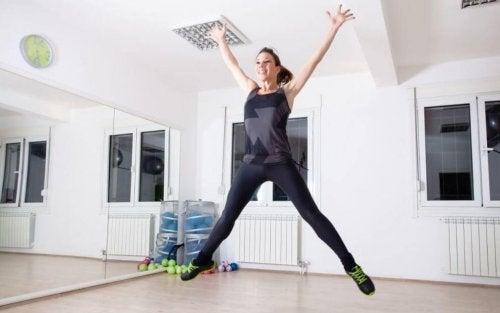 Exercícios cardiovasculares pulando com pernas abertas