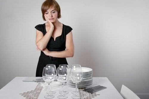 Mulher preocupada porque não espera ninguém para comer com ela