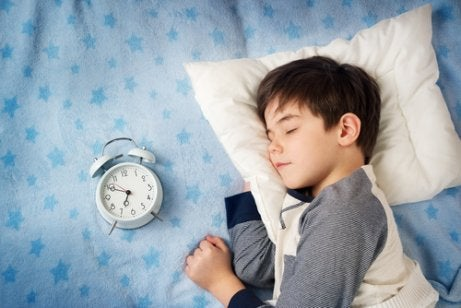 Menino dormindo ao lado do despertador
