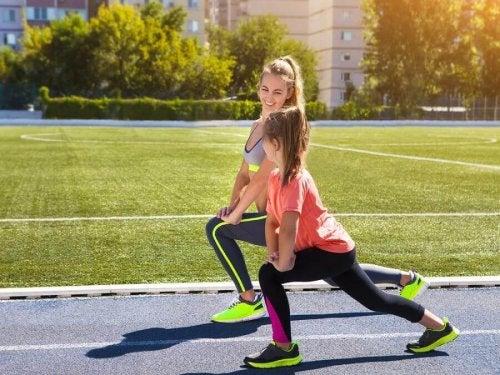 Mãe e filha fazendo exercícios