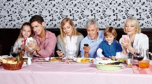 Refeição em família que está usando o celular