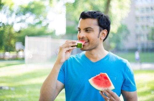 Homem comendo melancia