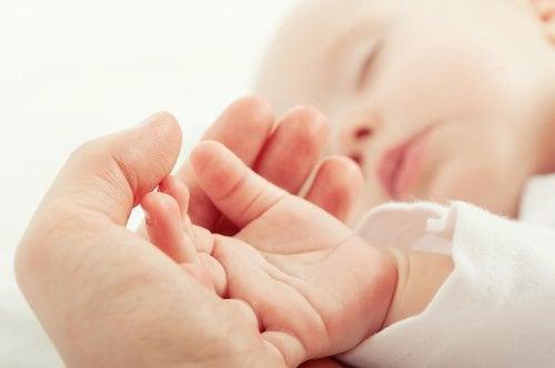 Mãe acariciando a mão de seu bebê