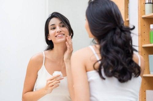 Mulher aplicando creme na pele