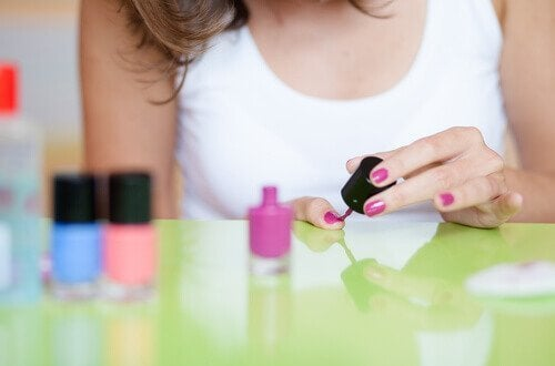 Mulher pintando as unhas semipermanentes