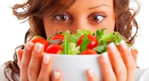 Mulher segurando salada grega