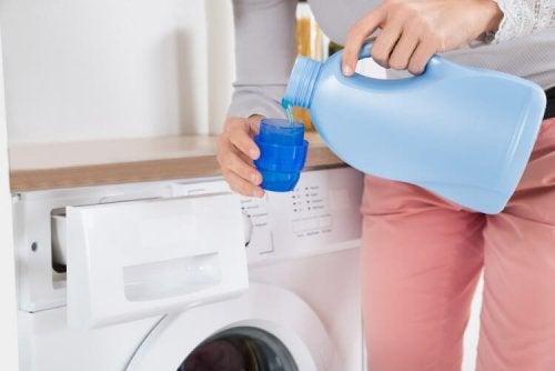 Mulher colocando amaciante na lavadora