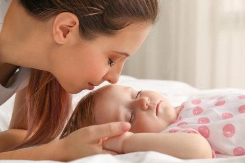 Mãe acordando a filha para trocar a fralda