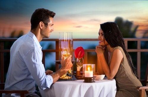 Casal relaxando no jantar com velas e óleos aromáticos
