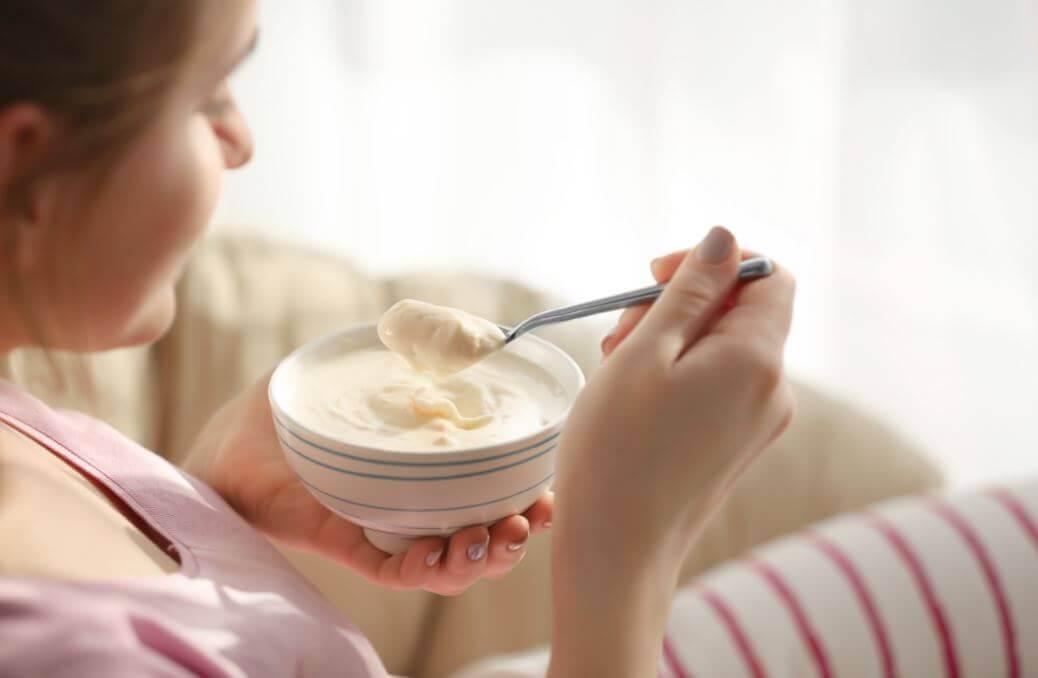mulher comendo iogurte caseiro