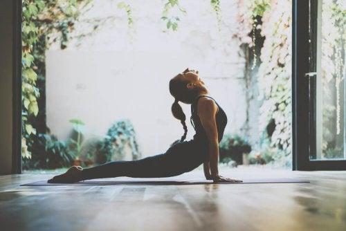 Mulher praticando ioga em casa