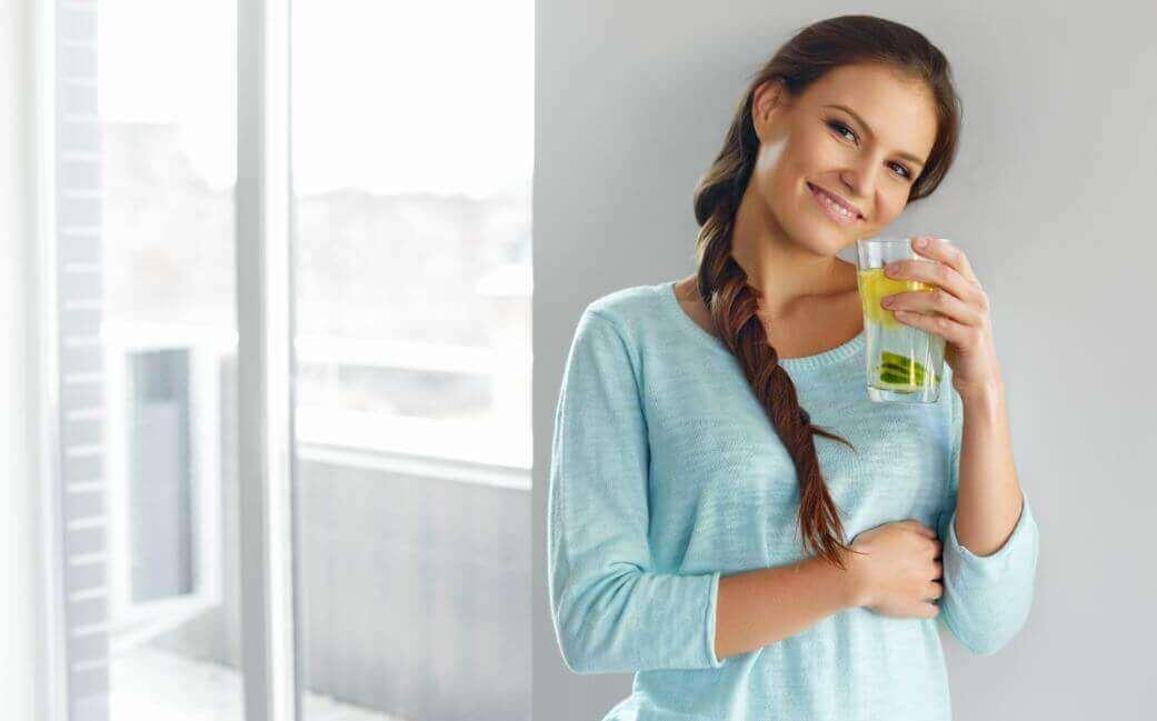Mulher tomando água com limão