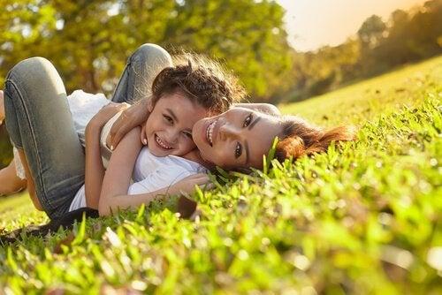 Mãe e filha abraçadas na grama
