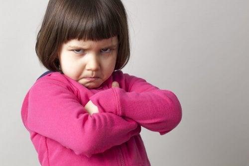 Criança de cara amarrada que não quer dar um beijo
