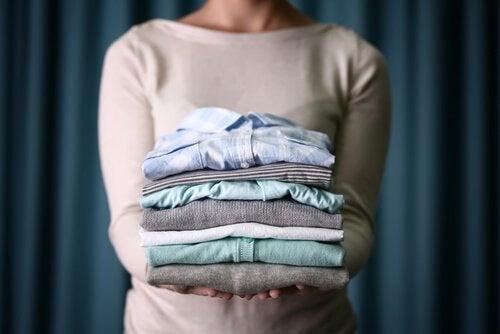 Mulher segurando roupas renovadas