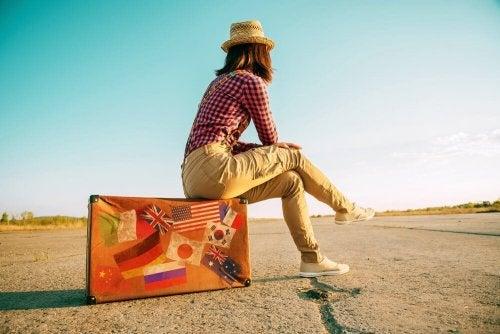 Mulher sentada em mala de viagem