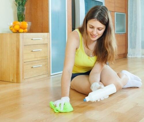 Mulher passando limpador cítrico no piso