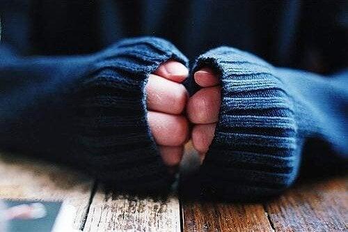 Pessoa escondendo o pé de atleta nas mãos