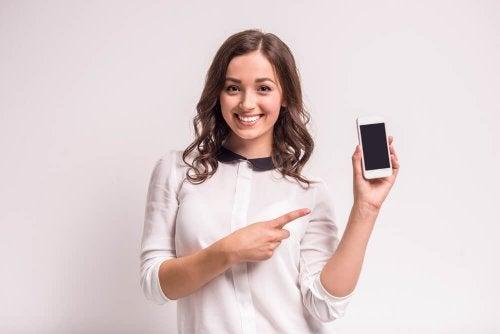 Mulher mostrando o celular pelo qual pode prognosticar os dias férteis