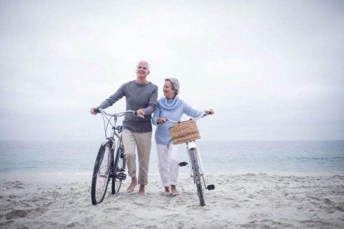 Casal de idosos andando de bicicleta na praia lutando contra a solidão