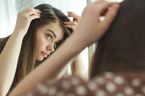 Moça fazendo um autoexame da pele do couro cabeludo