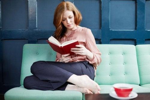 Moã lendo sentada no sofá