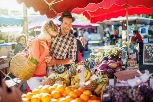 Casal escolhendo frutas para se cuidar sem renunciar à vida social