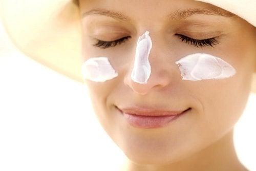 Mulher com protetor solar no rosto
