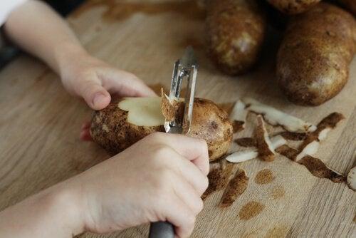 Mulher descascando batata para preparar um creme de batatas