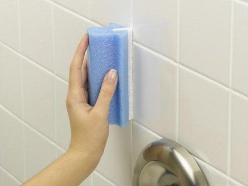 Mulher removendo resídous de sabão dos azulejos